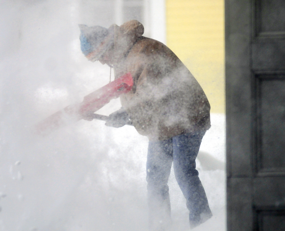 Cyrena Touchton attempts to shovel the sidewalk Tuesday in whiteout conditions at Harvey's Hardware in Gardiner.  Despite blowing snow and high winds, the store was open for customers in need of emergency supplies.