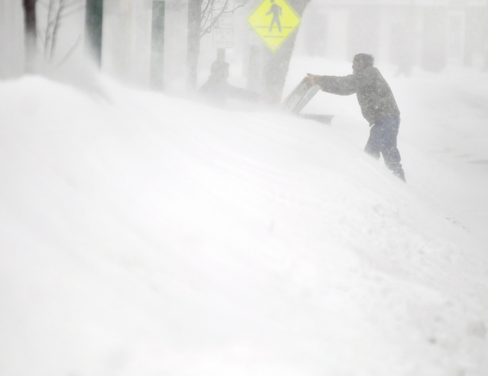 A man hands a box over a snowbank on Water Street in Gardiner. Drifts and banks several feet high obstructed people from crossing the road during the blizzard.