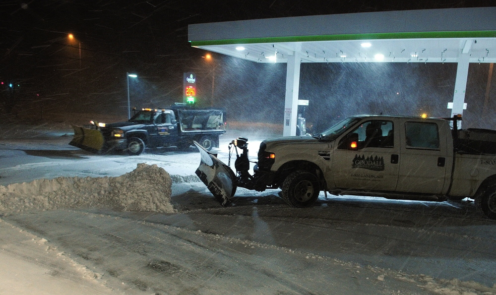 A plow truck driver clears the Cumberland Farms parking lot during a winter storm  around 6:20 a.m. on Tuesday in Gardiner.