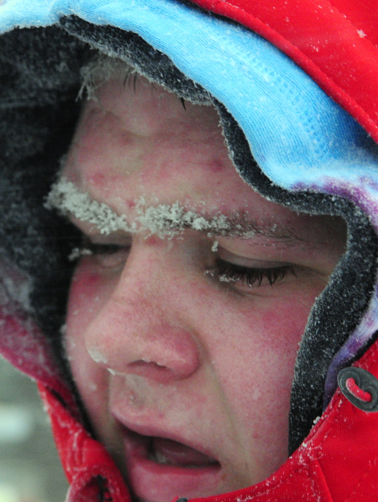 Snow freezes to the face of David Morris, 18 of West Gardiner, as he shovels at the West Gardiner Service Plaza Tuesday morning.