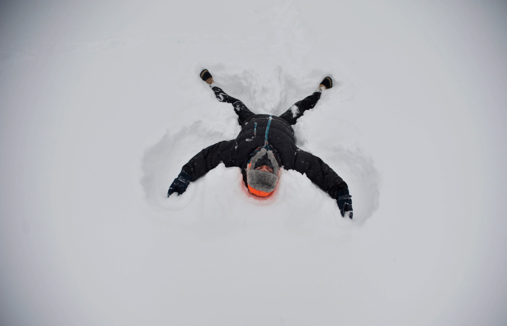 Seth Butler, a junior at Colby College, makes snow angels in front of Miller Library on campus in Waterville on Tuesday.