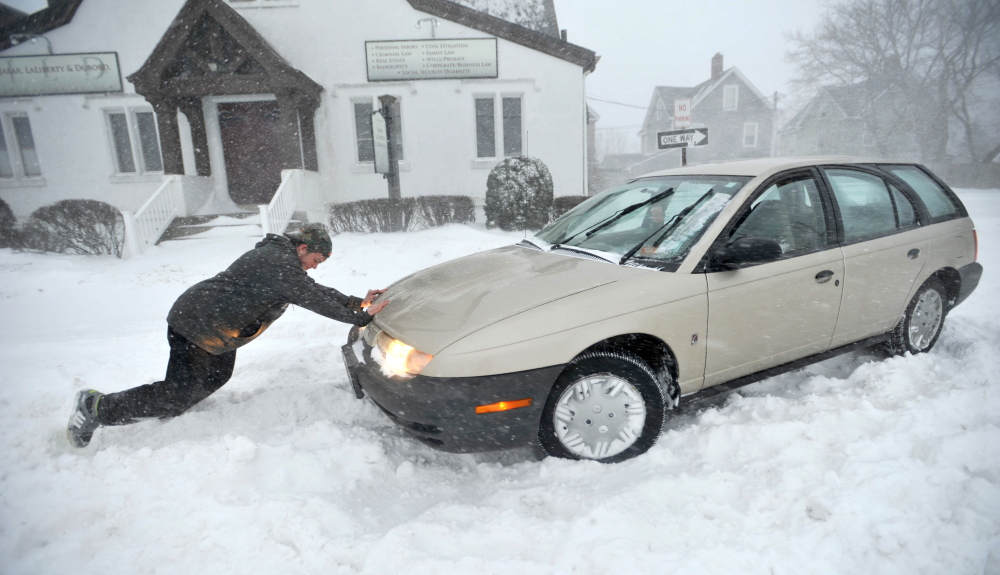 Zach Sanborn, 20, offers help to Ashley Fitzpatrick, who got stuck on Center Street in Waterville on Tuesday.