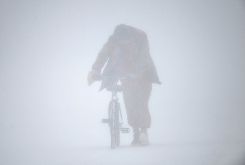 Eric Lopez walks his broken bike down Burleigh Street as snow falls in Waterville on Tuesday
