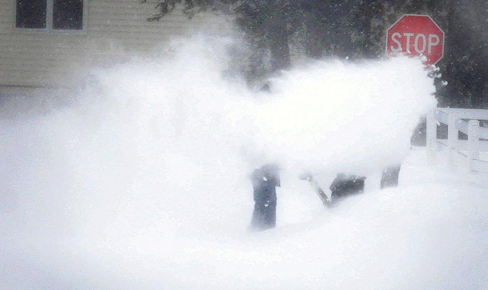 A man attempts to blow snow from his driveway in Augusta Tuesday.