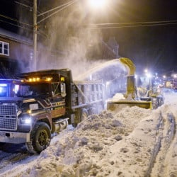 Road crews remove some of Tuesday's accumulation of snow from Commercial Street with an industrial-strength snowblower and a parade of dump trucks Wednesday as Portland embarked on the process of digging out of this week's blizzard.