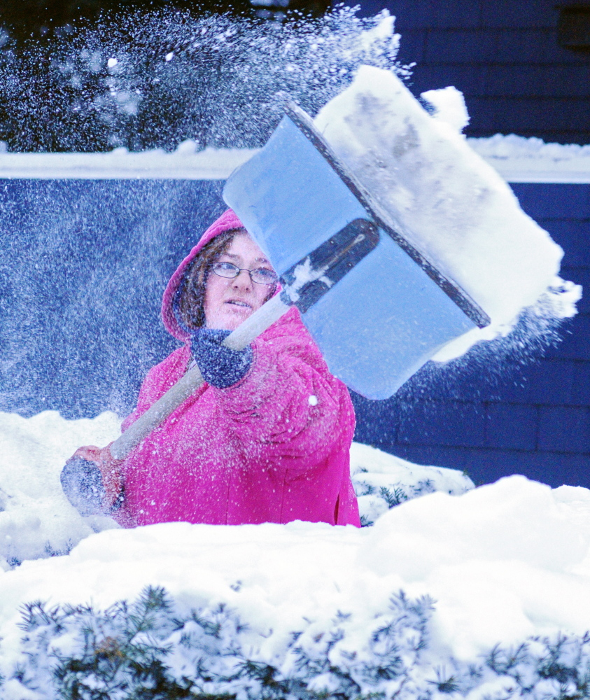 Crystal Callahan shovels the front of her home in Augusta on Wednesday following Tuesday's big storm.