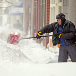 Scott Andrews shovels the sidewalk in front of a Water Street business in downtown Augusta around 8:05 a.m. on Wednesday, the day after a winter storm clobbered New England.