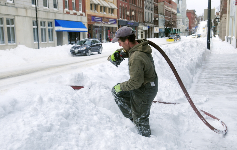 John Ramsay, of JR Energy Services, climbs over the snow pile between road and sidewalk after delivering fuel in front of a Water Street business in downtown Augusta around 8 a.m. Wednesday.