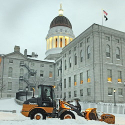 A front end loader pushes snow from a driveway on south side of the State House in Augusta around 6:50 a.m. on Wednesday. State and legislative offices are back open today following the storm.