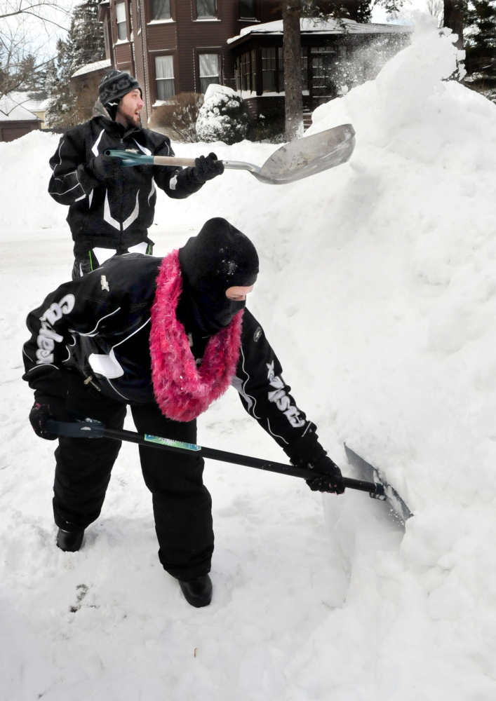 Throwing snow on to a six-foot snowbank on Wednesday, Andrea Shorty and Troy Eafrati clear snow from Tuesday's storm at their home in Waterville. People were out in force with shovels, snowblowers and plows clearing a foot or more of snow.