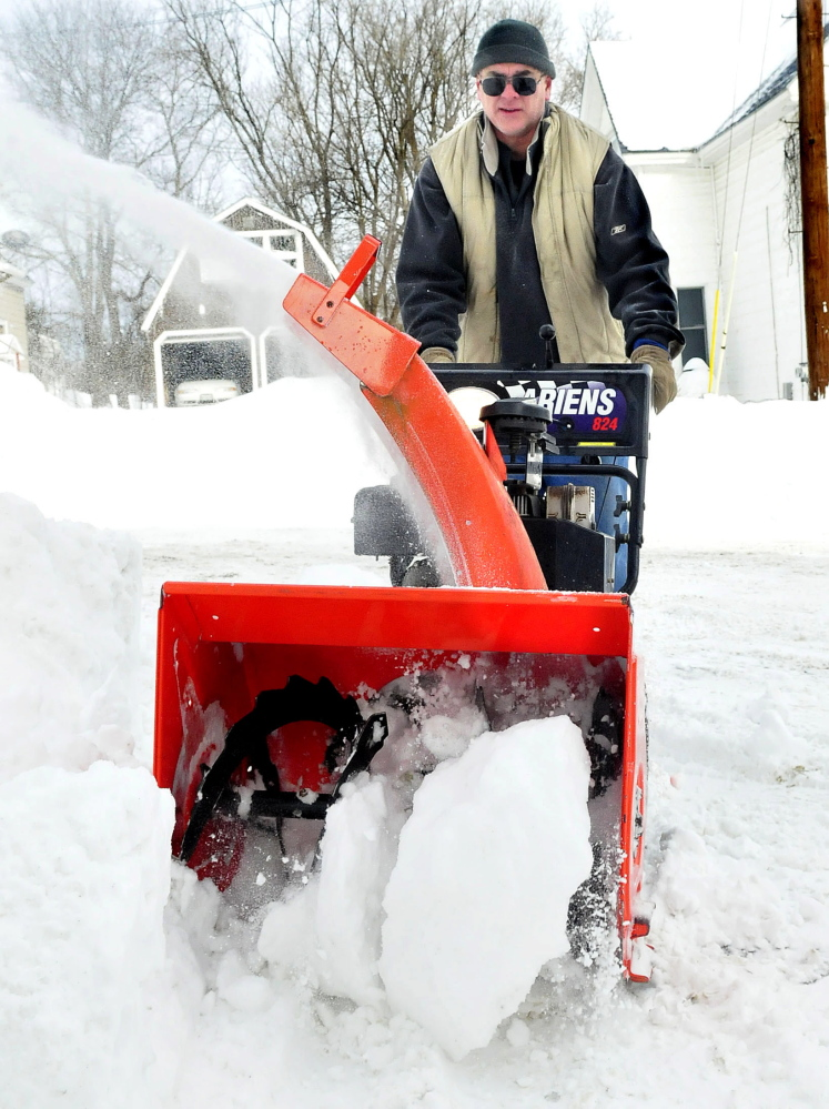 Tom St. Germain of the Chore Store clears large chunks of snow from the Waterville business parking lot Wednesday.