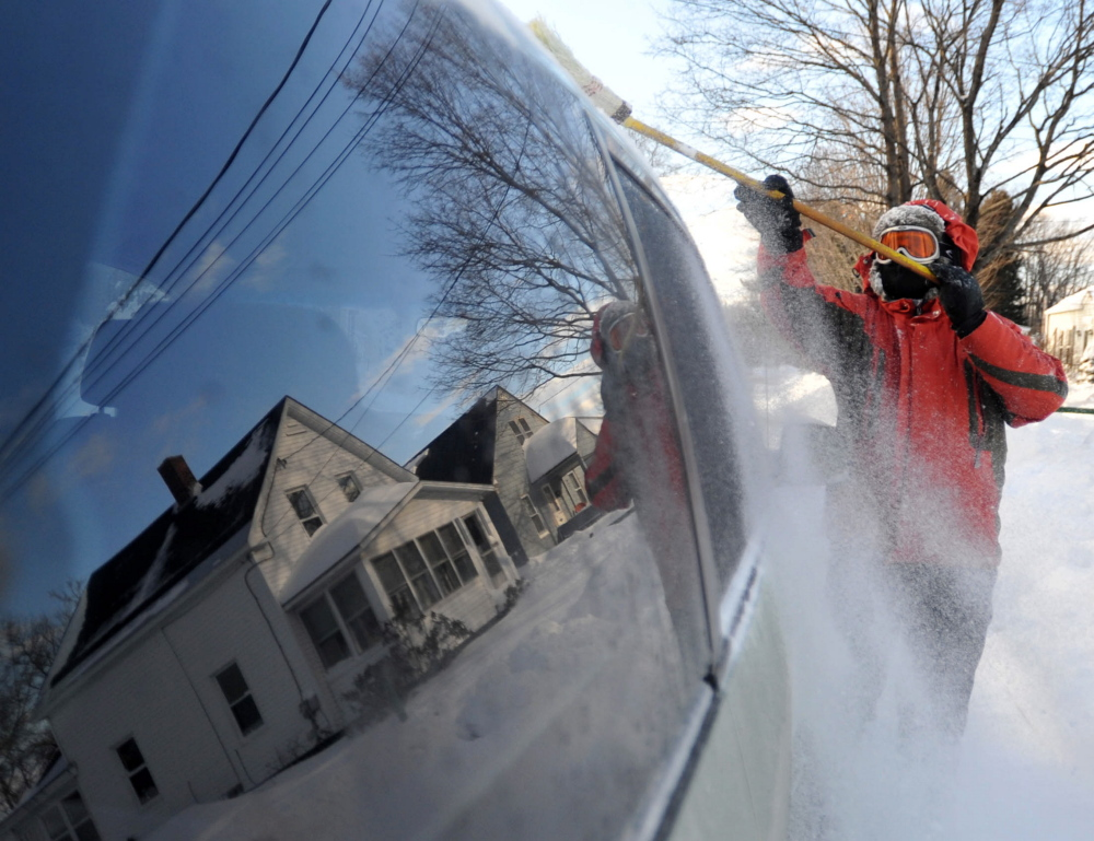 Jon Ramgren clears his minivan free of snow as he clears out his property on Edgemont Avenue in Waterville on Wednesday.