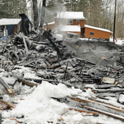 Steam rises from the remains of a house on Wednesday at 452 Mills Road in Whitefield. The house was destroyed by fire during the snow storm on Tuesday afternoon but firefighters from several departments stopped it from spreading to Michael Farrell's home, in background, about 50 feet away.