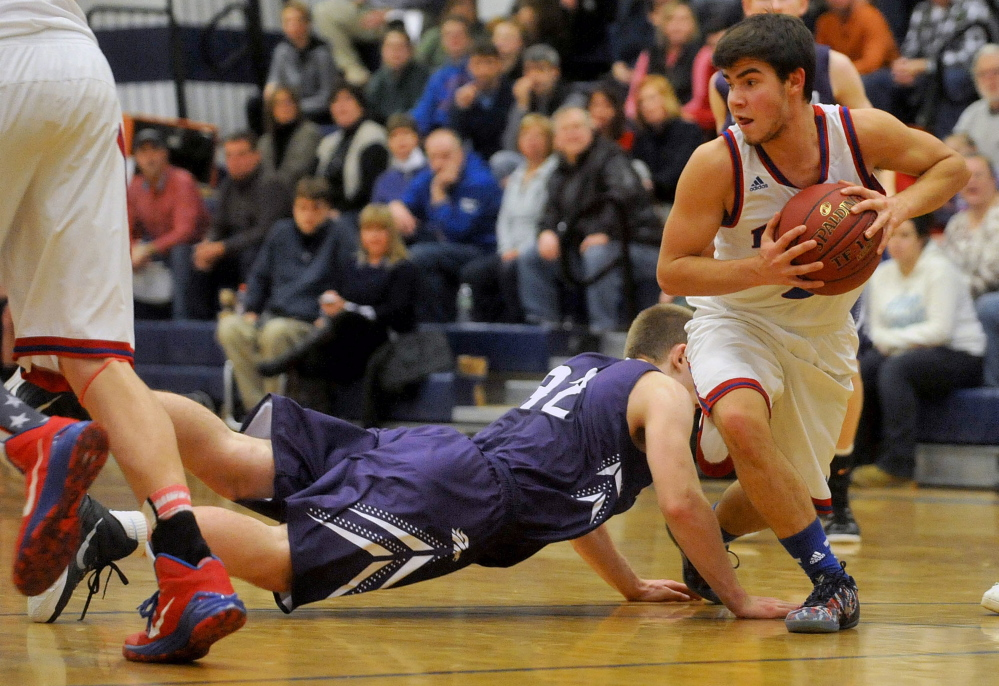 Messalonskee High School's Noah Caret (2) grabs the loose ball as Hampden Academy's Conary Moore (32) dives for it in the first half Wednesday in Oakland.