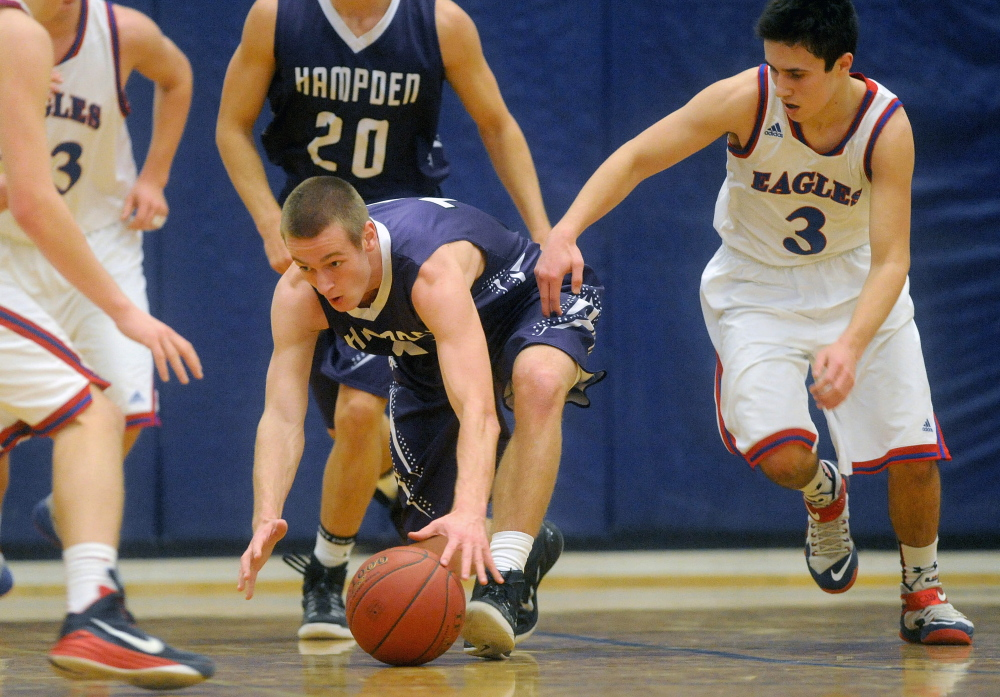 Hampden Academy's Jake Black, left, battles for the loose ball with Messalonskee High School's Sawyer Michaud, right, in the first half Wednesday in Oakland.