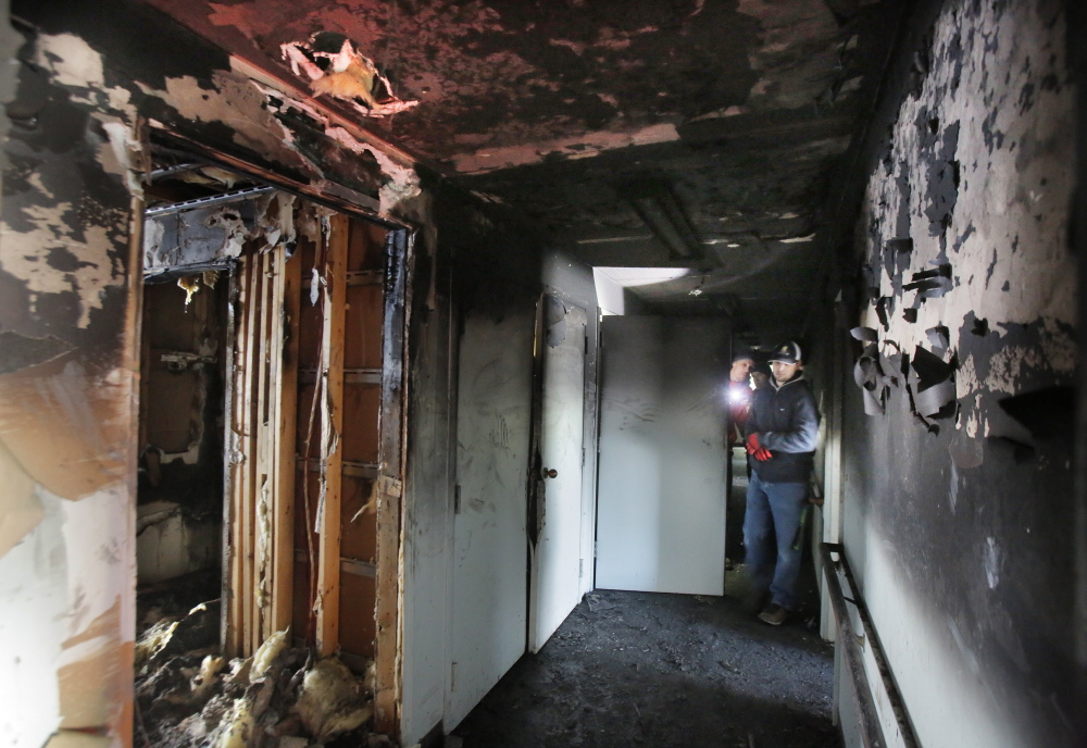 Workers survey damage in a hall at Centennial Place. Kevin Gerrish, property manager for Alpha Management, the building's owner, said one first-floor apartment was destroyed but the others can be cleaned.