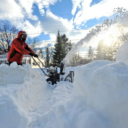 Jon Ramgren clears snow from his property on Edgemont Avenue in Waterville on Wednesday. Central Maine is digging out of nearly two feet of snow after a blizzard hit the area and more snow is on the way.