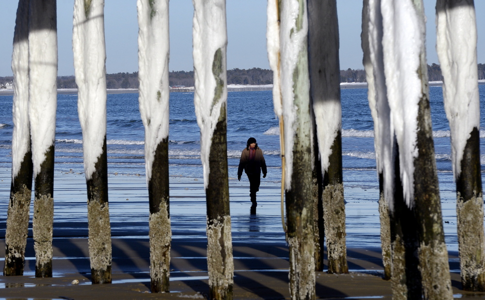 The Pier's pillars in Old Orchard Beach, covered in snow and ice, reflect the cold and windy conditions that have prevailed this week. The weather gave way to sun on Thursday, allowing Elisa Jacobs of Needham, Mass., to take a stroll along the beach.