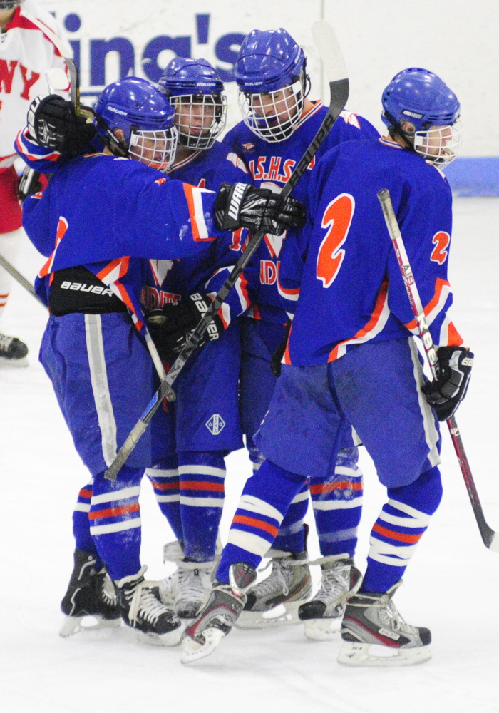 Members of the Lawrence/Skowhegan hockey team celebrate after Cody Martin scored to snap a 1-1 tie in an Eastern A game Thursday at the Bank of Maine Ice Vault in Hallowell.