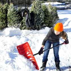 Staff photo by David Leaming Thomas College student Sydney Sennett digs a path in the snow for the Winter Carnival Christmas tree maze at the Quarry Road Recreation Center in Waterville this Saturday.