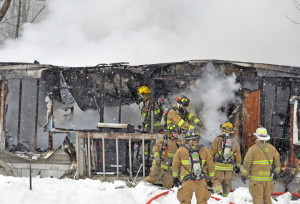 Firefighters look for hot spots after fire destroyed a mobile home Friday at 2968 North Belfast Ave. in Augusta.
