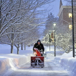 Ethan Weeks, an employee at Colby College, clears snow from the walkways on campus as a winter storm dumps another nearly a foot of snow in Waterville on Friday.
