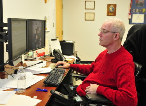 Augusta Police Chief Robert Gregoire works in his office Friday at police headquarters in Augusta. He has gained enough strength and dexterity in his hands recently to be able to use a computer mouse again.
