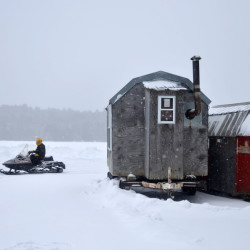 A snowmobiler rides his machine past two ice shacks Friday on Lake George in Skowhegan.