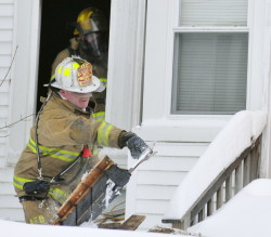 Augusta Deputy Fire Chief Dave Groder throws boards that another firefighter working inside passed out to him Saturday at 101 Green St. in Augusta. Firefighters tore out the boards to find any fire that might be remaining in floors and walls.