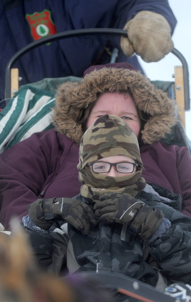 Mary Riopelle bundles up with her son Donald on Saturday as they brave the cold for a dog sled ride at the annual Winter Carnival at the Quarry Road Recreational Area in Waterville.