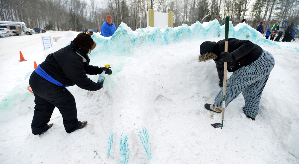 Jennifer Olsen, left, and Serena Sanborn create a dragon out of snow Saturday as part of the snow sculpture contest at the annual Winter Carnival at Quarry Road Recreational Area in Waterville.