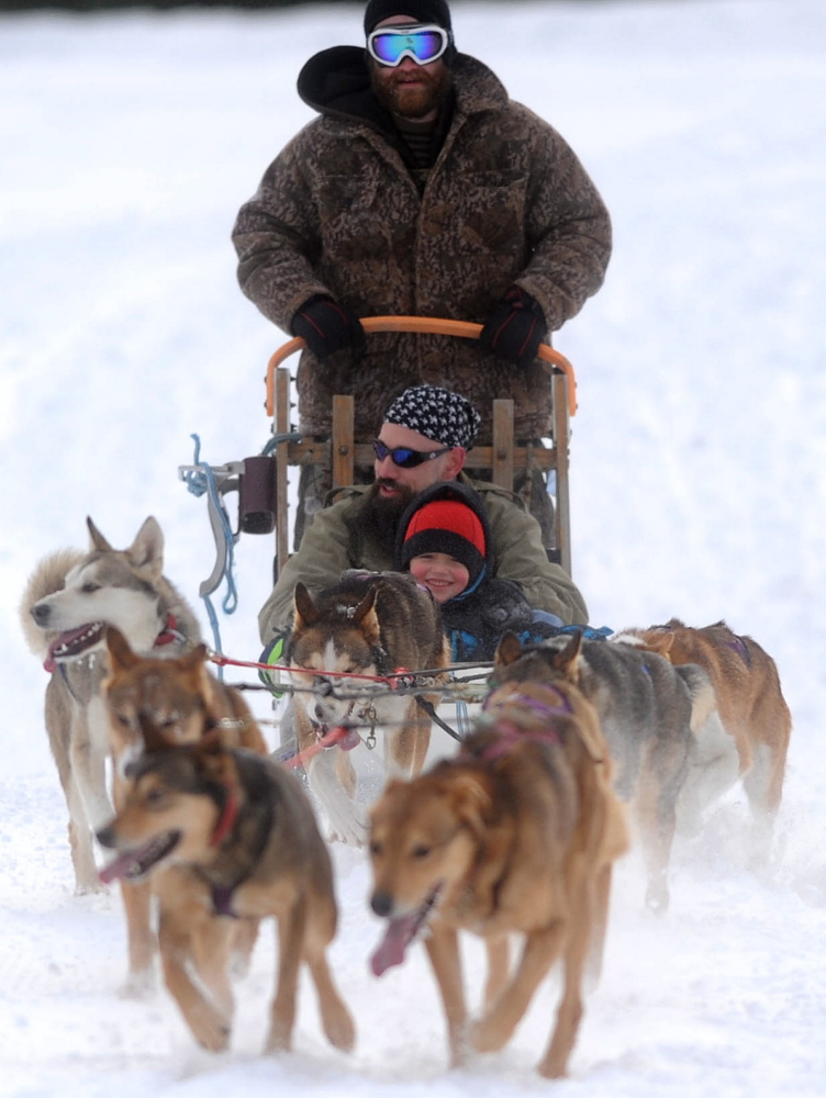 Tim Lonergan, a musher with Heywood Kennels in Augusta, drives a dog sled Saturday with Dominic Bunker and his nephew Landyn Cummings, 5, for the annual Winter Carnival at Quarry Road Recreational Area in Waterville.