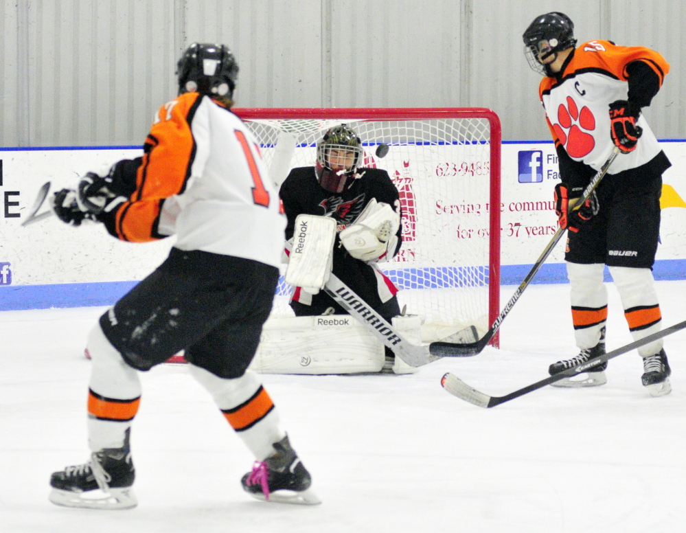 Gardiner's Reid Cotnoir, left, takes a shot that starts the play ending with a goal by teammate Logan Peacock, 15, right, to put Tigers up 1-0 in first period during a game against Maranacook/Winthrop on Saturday at the Bank of Maine Ice Vault in Hallowell.