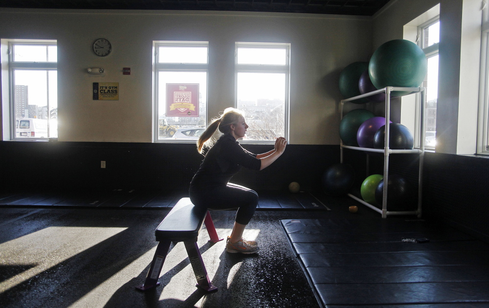 """Rachel Fisk of Portland does squats while working out at Planet Fitness in Portland on Thursday. """"I've been struggling lately with fitting it into my schedule and getting motivated,"""" she said. Photos by Jill Brady/Staff Photographer"""