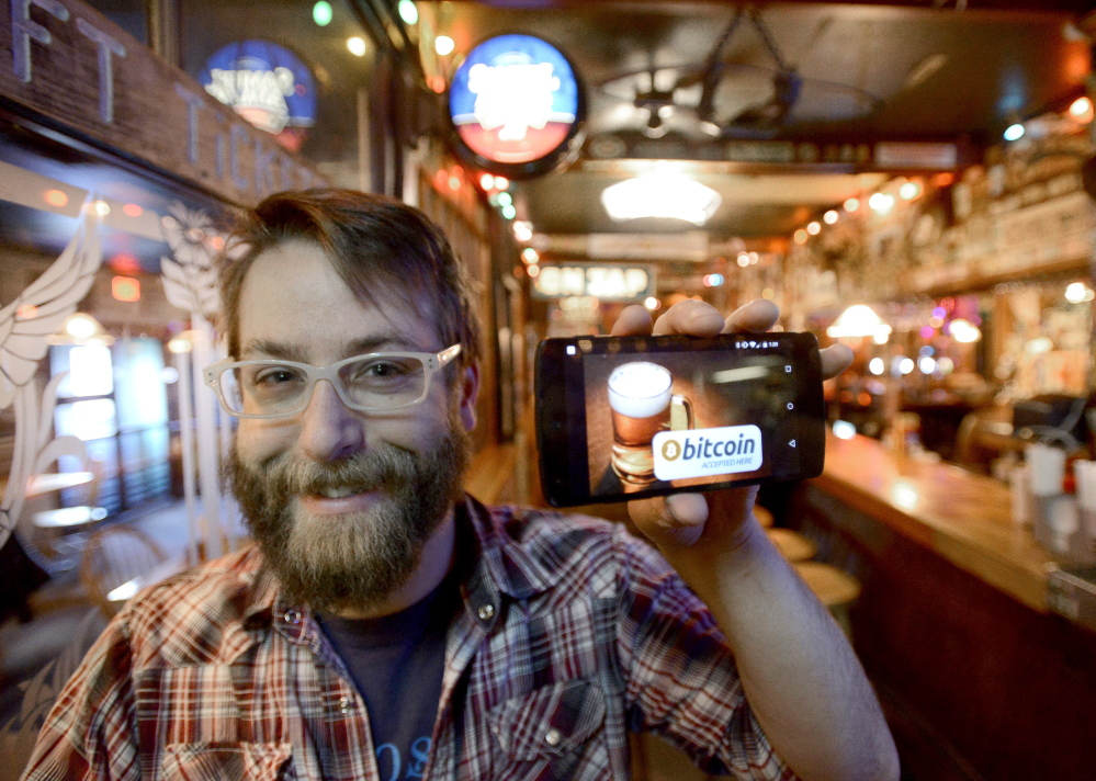 Dave Foster, media marketing manager at The Great Lost Bear in Portland, holds up his mobile phone displaying a bitcoin app that can be used for payment at his restaurant. John Patriquin/Staff Photographer