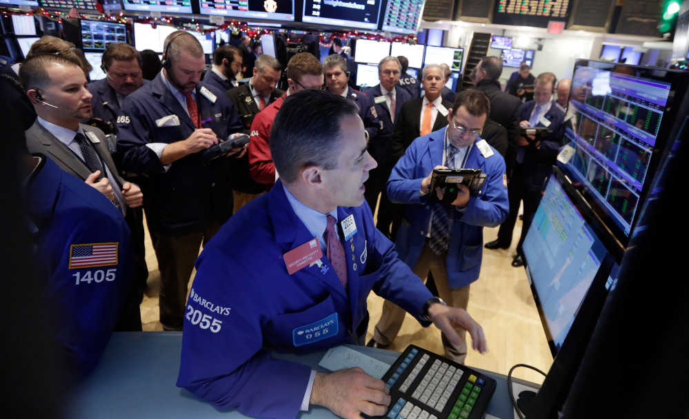 Traders gather at the post of specialist Jason Hardzewicz, foreground, on the floor of the New York Stock Exchange on Tuesday. The Associated Press