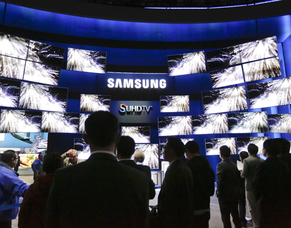 The Samsung booth draws a crowd Tuesday at the gadget show in Las Vegas. Some of the company's new sets make colors purer and the screen brighter. The Associated Press