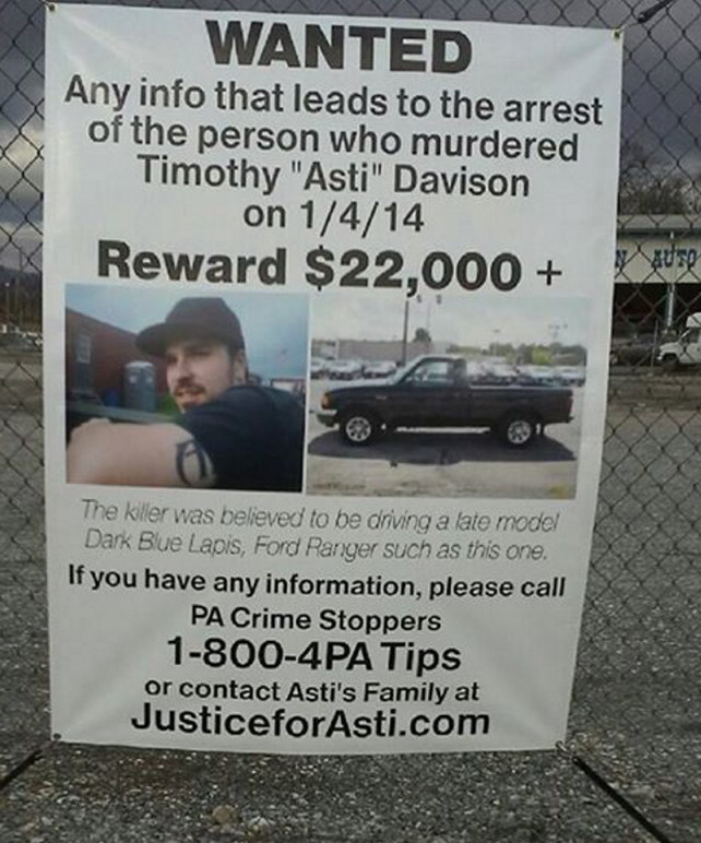 In this Jan. 6, 2015, photo,  a sign posted on a fence in Pennsylvania helps to keep the death of Timothy 'Asti' Davison in the public eye.