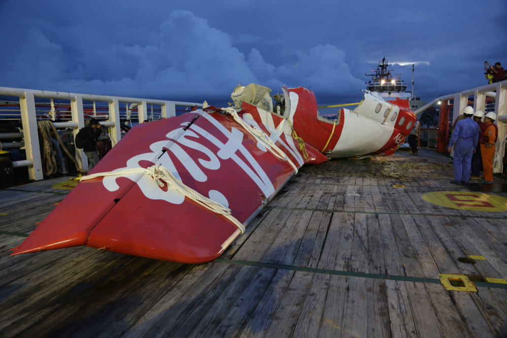 Parts of AirAsia Flight 8501 is seen on the deck of rescue ship Crest Onyx at Kumai port in Pangkalan Bun, Indonesia, on Sunday. A day after the tail of the crashed AirAsia plane was fished out of the Java Sea, the search for the missing black boxes intensified Sunday with more pings heard. The Associated Press
