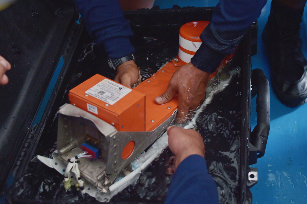 Indonesian divers hold the flight data recorder of AirAsia Flight 8501 on the navy vessel KRI Banda Aceh on Monday. Divers later retrieved the cockpit voice recorder, a key find that should help investigators determine what caused the aircraft to plummet into the Java Sea. The Associated Press