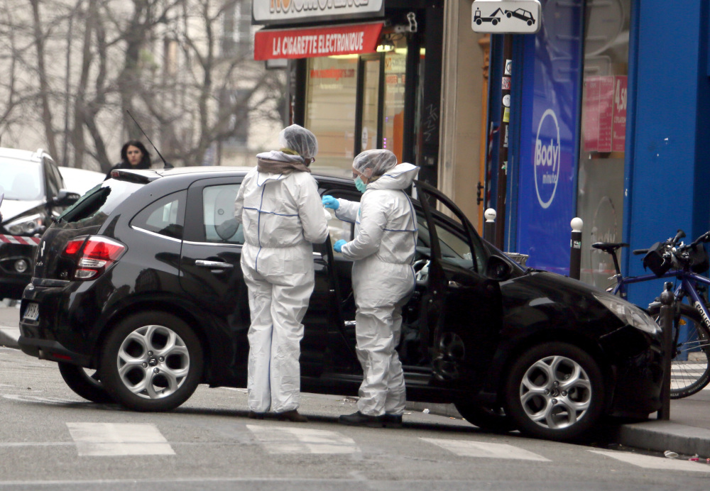 Forensic experts examine the car believed to have been used by the gunmen who attacked Charlie Hebdo's office in Paris on Jan. 7. A week after the terror attacks, investigators are still unraveling the complex, overlapping contacts among the gunmen and their suspected accomplices. Jan. 7, 2015, File Photo / The Associated Press
