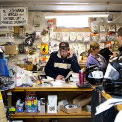 Wayne Keniston handles a call at his Falmouth store while shoppers anticipating good riding browse for snowmobile gear.  Gabe Souza/Staff Photographer