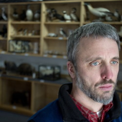 Eric Topper, director of education for the Maine Audubon, talks about the theft from the group's mounted collection, shown behind him in Falmouth on Wednesday. Gabe Souza/Staff Photographer