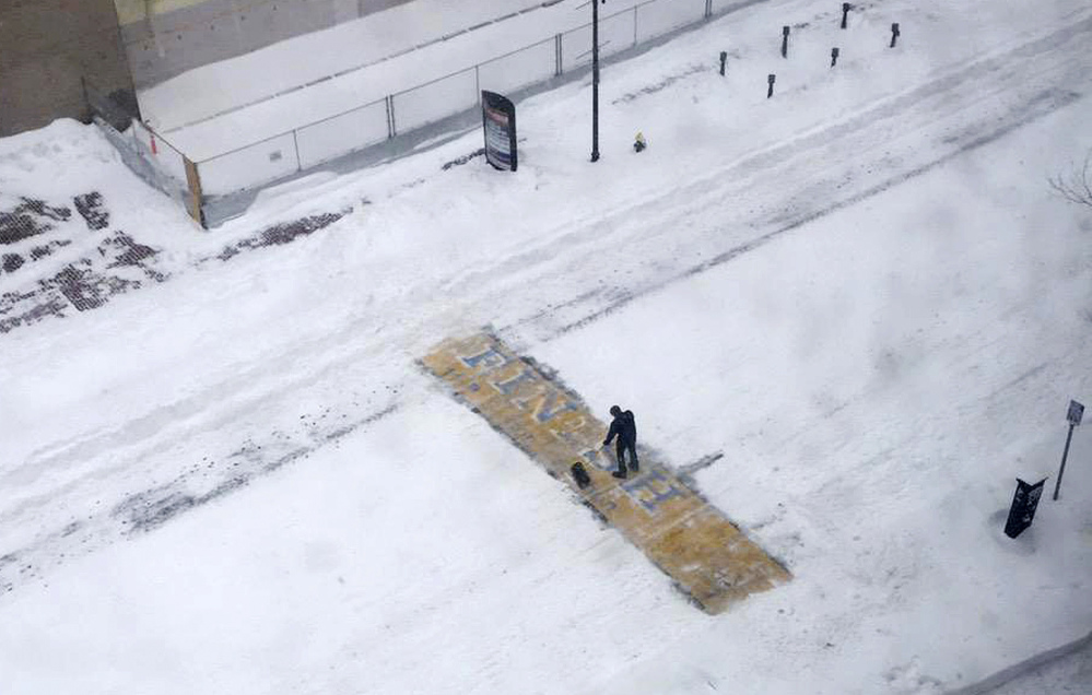 Chris Laudani, a bartender at the Back Bay Social Club, shovels snow from the Boston Marathon finish line on Boylston Street in Boston during Tuesday's winter storm that slammed eastern Massachusetts with as much as 2 feet of snow. The Associated Press