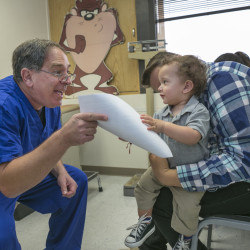 Pediatrician Charles Goodman talks with Carmen Lopez and her 18-month-old son Daniel after he was vaccinated at Goodman's practice in Northridge, Calif., Thursday. The Associated Press