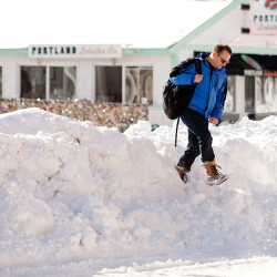 Scott Watson of Portland climbs over the high bank of snow in the middle of Commercial Street to make his way to work Wednesday.
