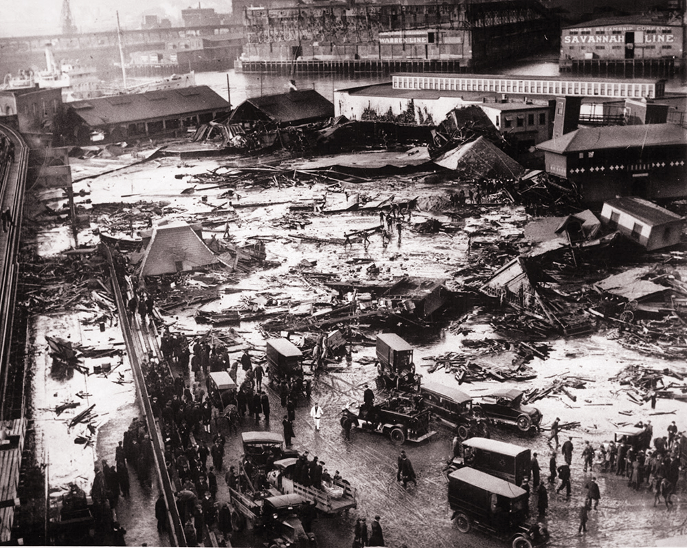 Twenty-one people were killed when a tank of molasses ruptured and exploded, sending a 40-foot wave of the liquid down Boston's Commercial Street at a speed of 35 mph. Wreckage of the collapsed tank is visible in the background, center, next to the light-colored warehouse. The elevated railway structure is visible at far left and the North End Park bathing beach is to the far right. Boston Public Library photo