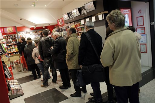 People queue up to buy the new issue of Charlie Hebdo newspaper at a newsstand in Paris Wednesday.Charlie Hebdo's defiant new issue sold out before dawn . The Associated Press