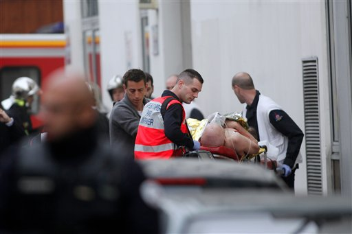An injured person is treated by nursing staff outside the French satirical newspaper Charlie Hebdo's office, in Paris, Wednesday. The Associated Press