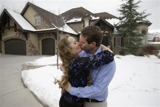 "Jeff Bennion and his wife Tanya kiss in front of their home near Salt Lake City. Their relationship is featured in TLC's upcoming reality show ""My Husband's Not Gay."" The Associated Press"